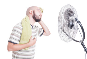 No air conditioning sweaty man in front of fan