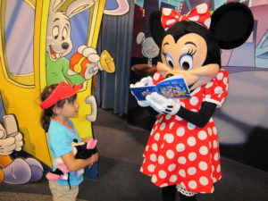child waiting on Minnie Mouse to sign her autograph book, Disney - How to Save Money