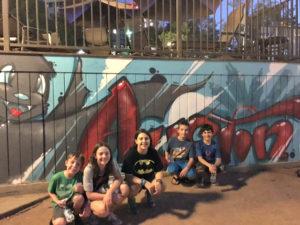 children in Austin near street art of bat
