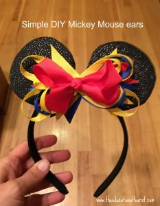 Mickey Mouse ears on a headband with yellow, blue and red bow