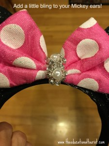 Mickey Mouse ears on a headband with pink and white polka dotted bow with crystal and pearl decoration in center of bow