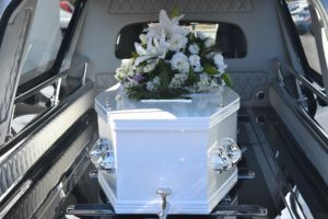Casket in hearse with white flowers