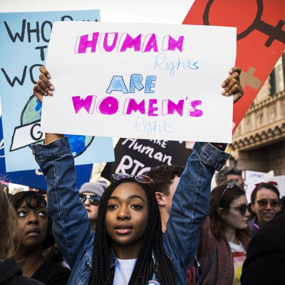 IMAGE COURTESY/VOX. A black woman holding a placard during a women's rights protest.