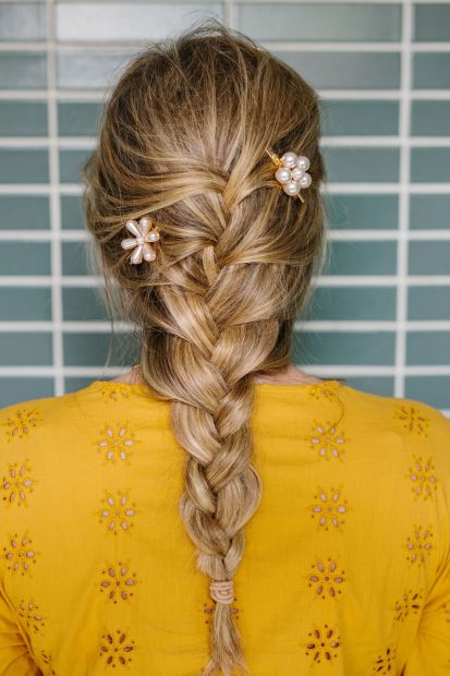 A French braid with pearl pins