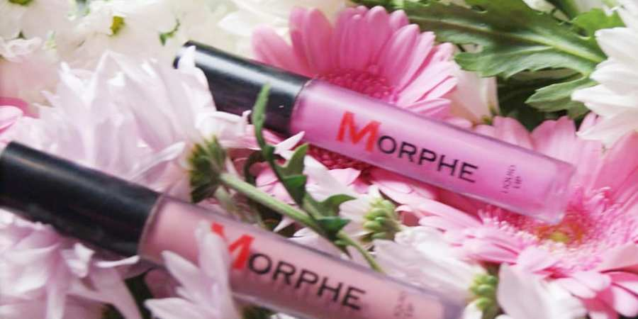 Morphe lipsticks in brown and pink sat on a bed of flowers
