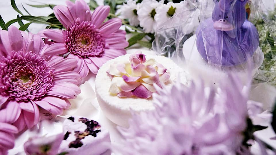 Bath bombs of all shapes surrounded by flowers