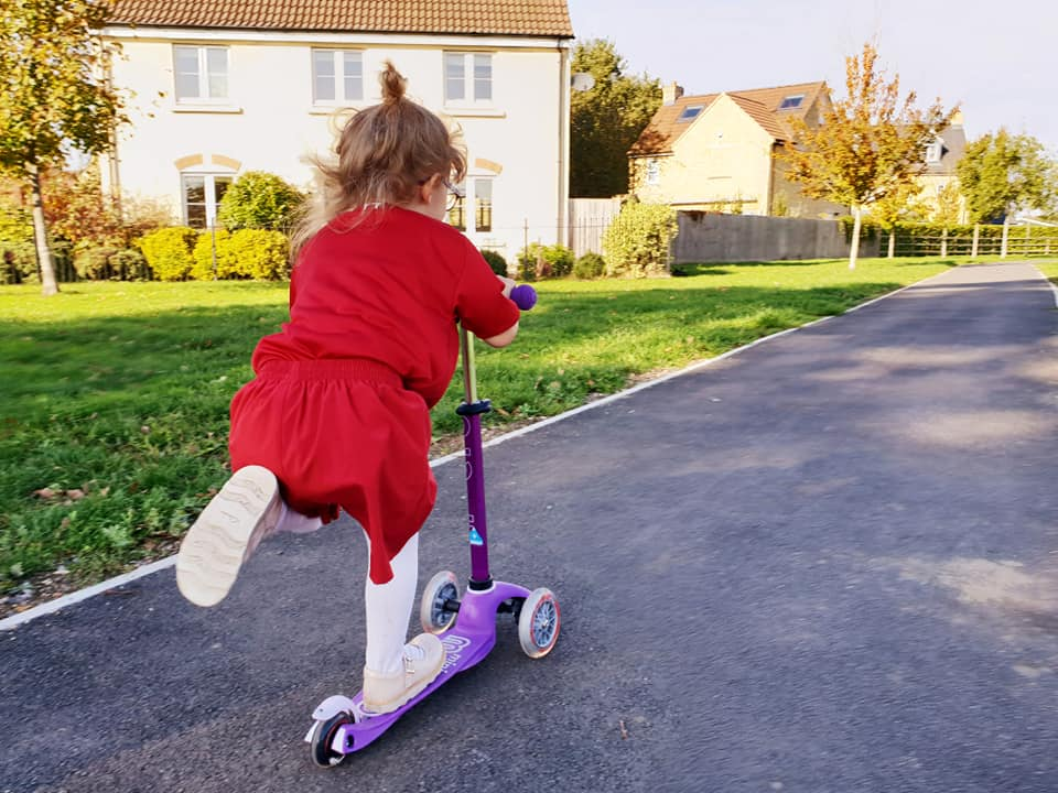 Shaniah riding her scooter in her liverpool fc kit down a track.