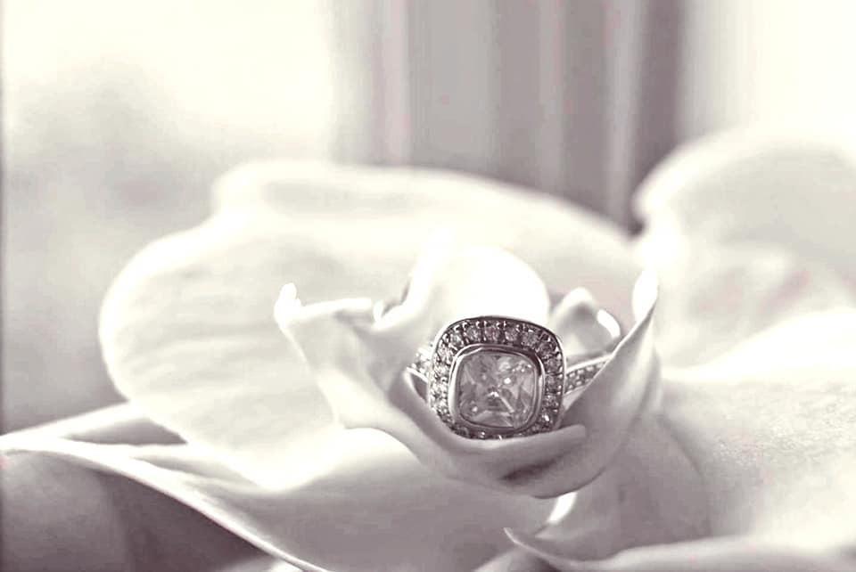 Black and white photo of a square ring sat on a flower.