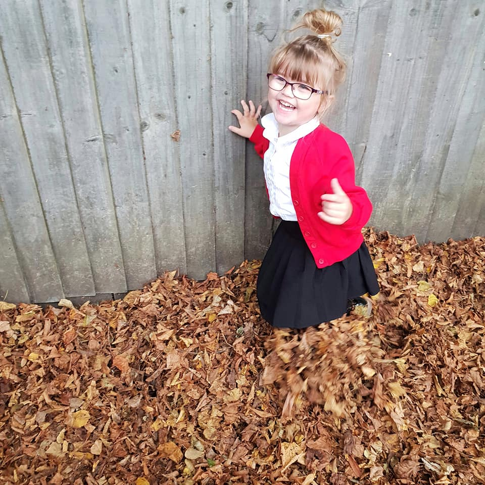 Shaniah is standing in a pile of leaves smiling with her thumb up.