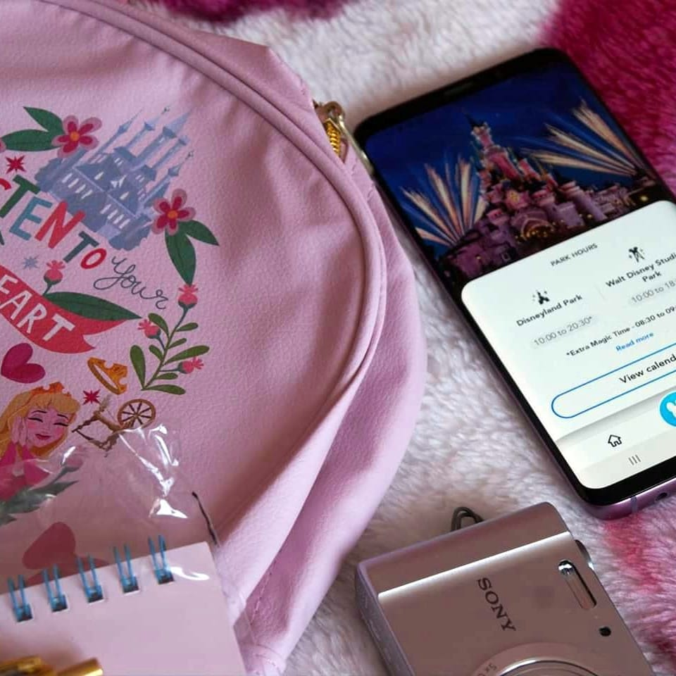 flatlay of disney backpack and phone with the app open