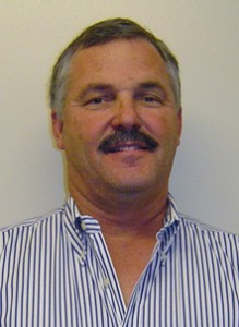 Headshot of veterinarian Kent Fowler in a blue and white-striped shirt.