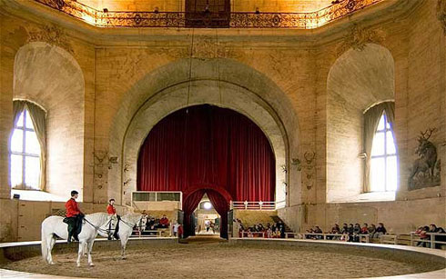 Interior of the Grand Stables during a live riding demonstration.