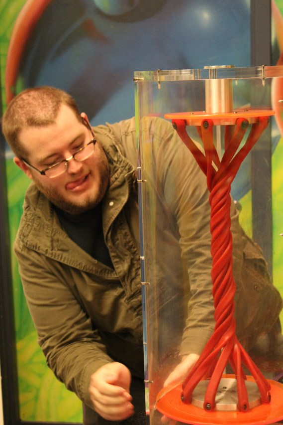 """There was an exhibit where you could """"test out"""" different things. Here's Adam seeing how tight he can twist the elastic."""