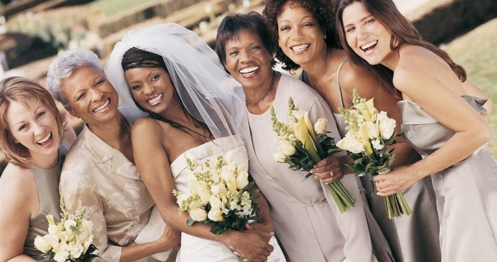 Bride, bridesmaids and mothers in different gowns at a wedding reception