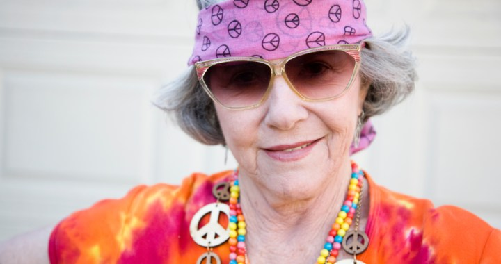 older woman wearing sunglasses, headband and love beads