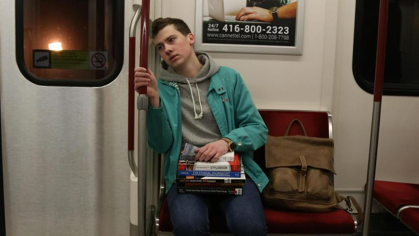 A student commuter sits in a subway car, looking exhausted
