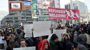 "Protestors march down the streets at Yonge and Dundas. A sign that reads, ""Refugees Welcome"" is held"
