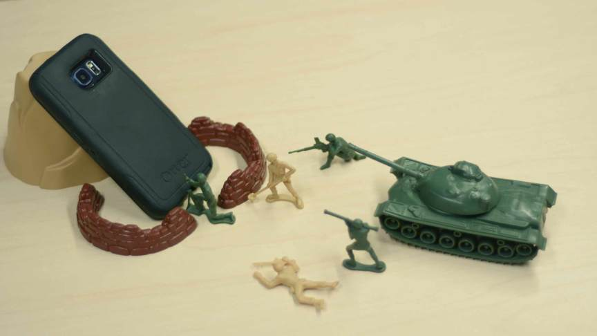 Toy army soldiers fighting a cell phone