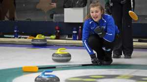 A curling player watches the ice
