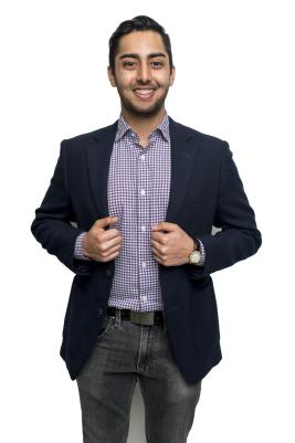 Faruqi stands in front of a white backdrop, hands on the front of his jacket.