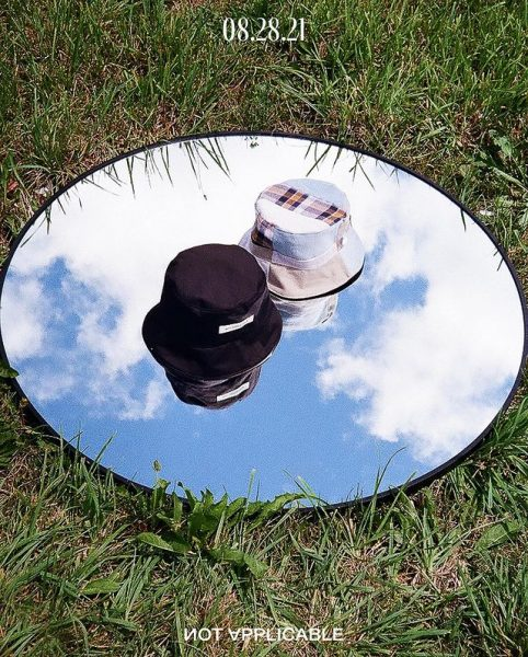 Two bucket hats, one black and one white, on a mirror placed on grass while its facing the sky