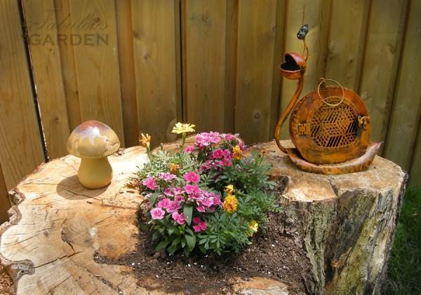 Plants, a ceramic mushroom, and a metal snail sit on a tree stump