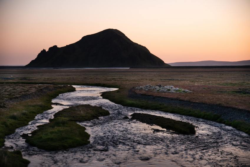 The melt water from the glaciers of Iceland passes over a low grassy pain under the midnight sun of the far north.
