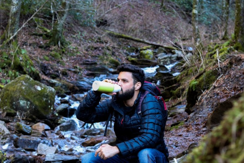 Tim McKenna drinking from water bottle near stream