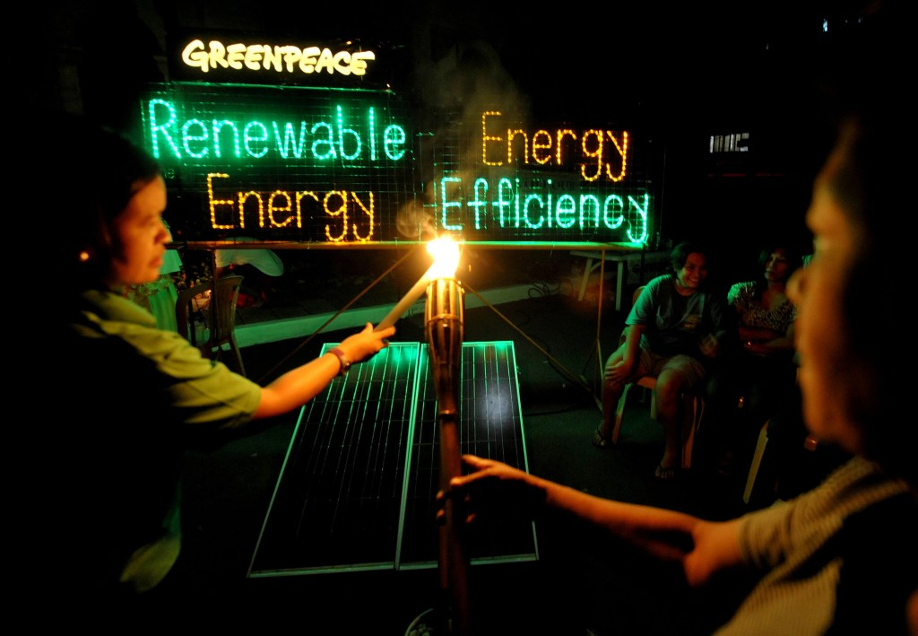 """As part of the Earth Hour program in Malate Church, volunteers from the community and the environment group Greenpeace light up candles and display an LED (light emitting diode) installation, powered by solar electricity, spelling the words """"Renewable Energy. Energy Efficiency"""" to highlight the need for an 'Energy Revolution' to call for solutions to climate change. Greenpeace is using the opportunity during this year's Earth Hour to call attention to the need for commitment from political leaders to support the massive shift from dependence on climate change-causing fossil fuel to renewable energy and energy efficiency technologies."""