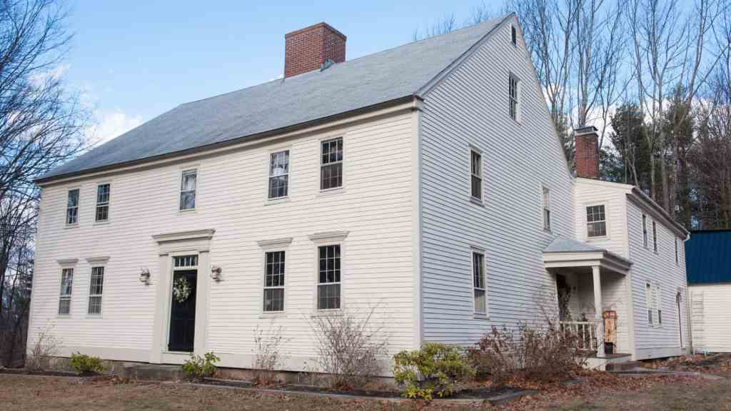 A large colonial style house with lots of windows on acreage.