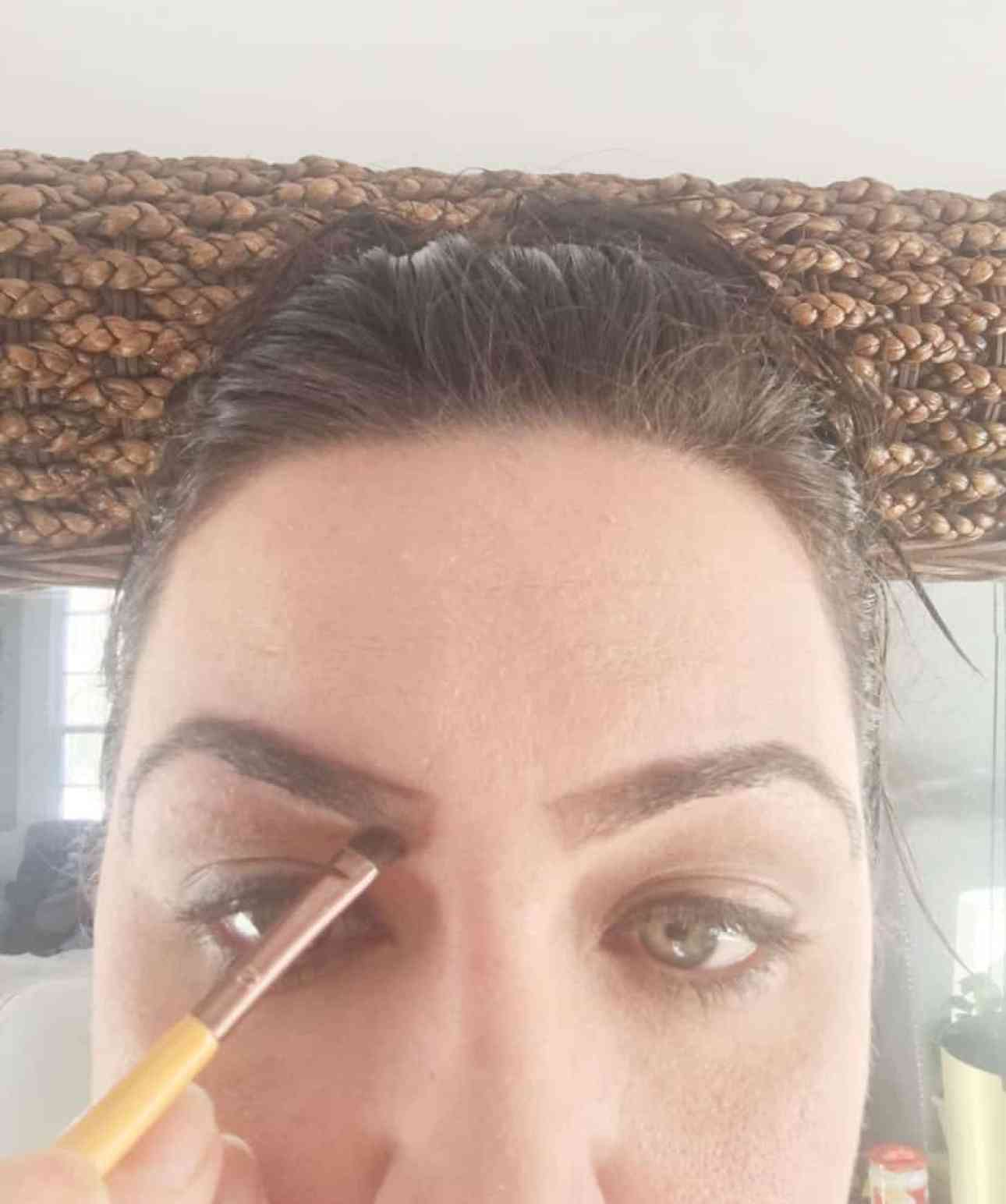 Filling in the eyebrows with a small angled brush.