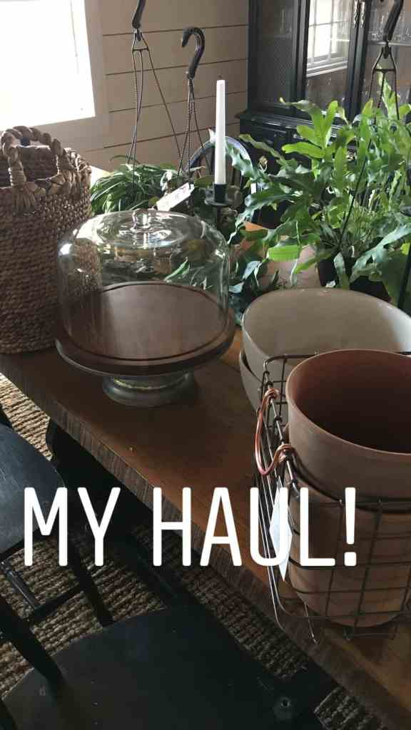 Plants, a cake stand and a metal basket on the counter.