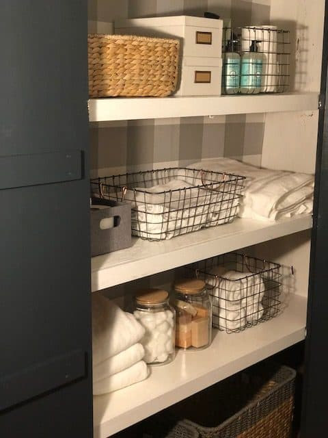 An open closet door with baskets and bathroom supplies.
