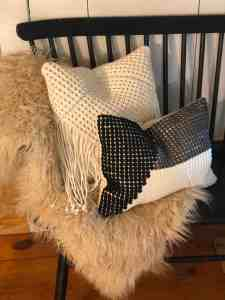 Two pillows on faux fur on the bench.