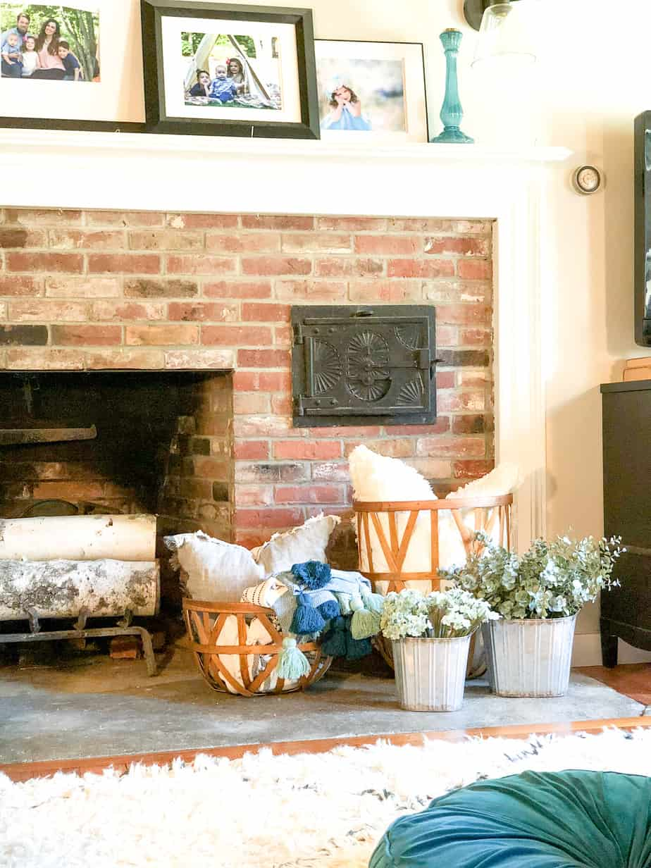 The galvanized buckets in front of the fireplace with eucalyptus in them.