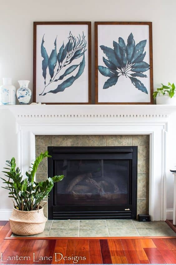 A fireplace mantel in white with large pictures of leaves that have a brown frame around them sit on top of the mantel.