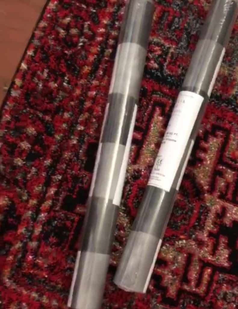 Wallpaper rolls on a rug with red and black tones.