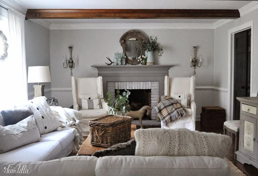 A grey and white mantel with armchairs flanking the fireplace.   There is a wood beamed ceiling.