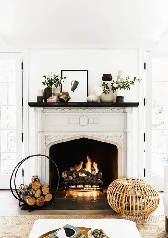 A lit fire is in the fireplace, there are vases filled with flowers and greenery and a black and white picture sits on the mantel.