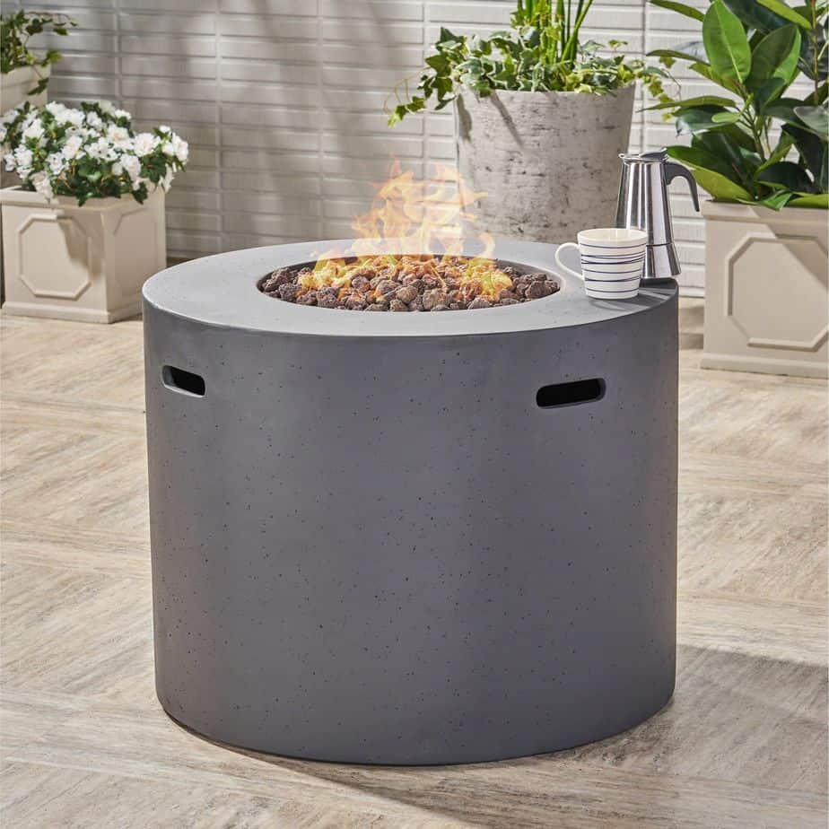 A propane fire pit with a round covering in grey.  There is a coffee cup sitting on the edge of the fire pit.