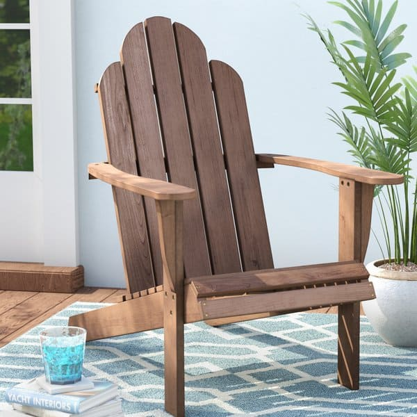 A wooden Adirondack chair on a blue and white outdoor rug.