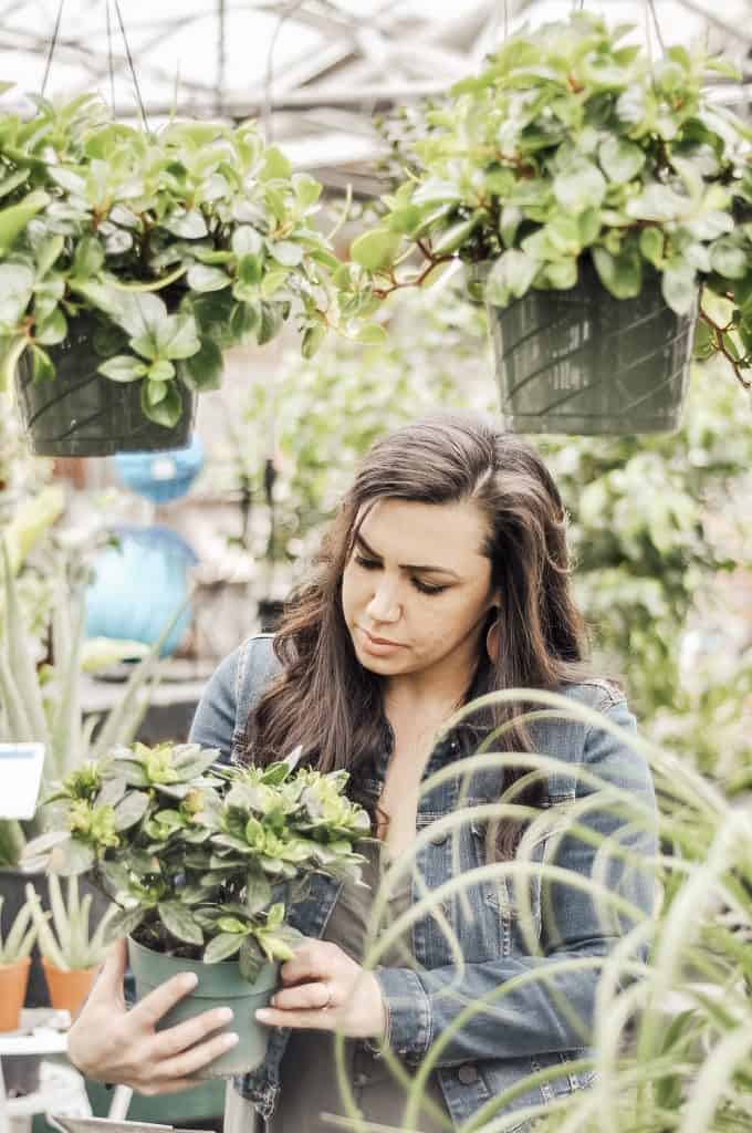 Woman looking at plant in the nursery.