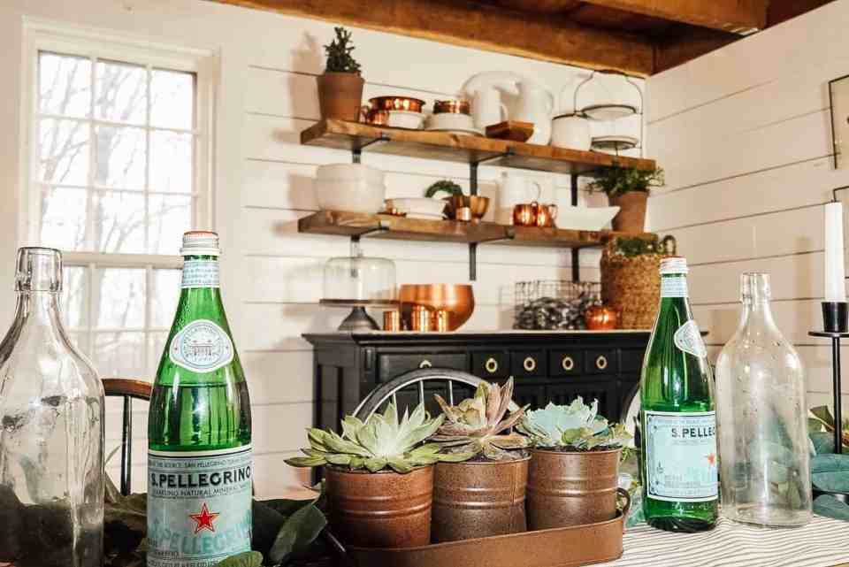 Dining table and open shelving behind the table.  There is Pellegrino on the table, as well as succulents.