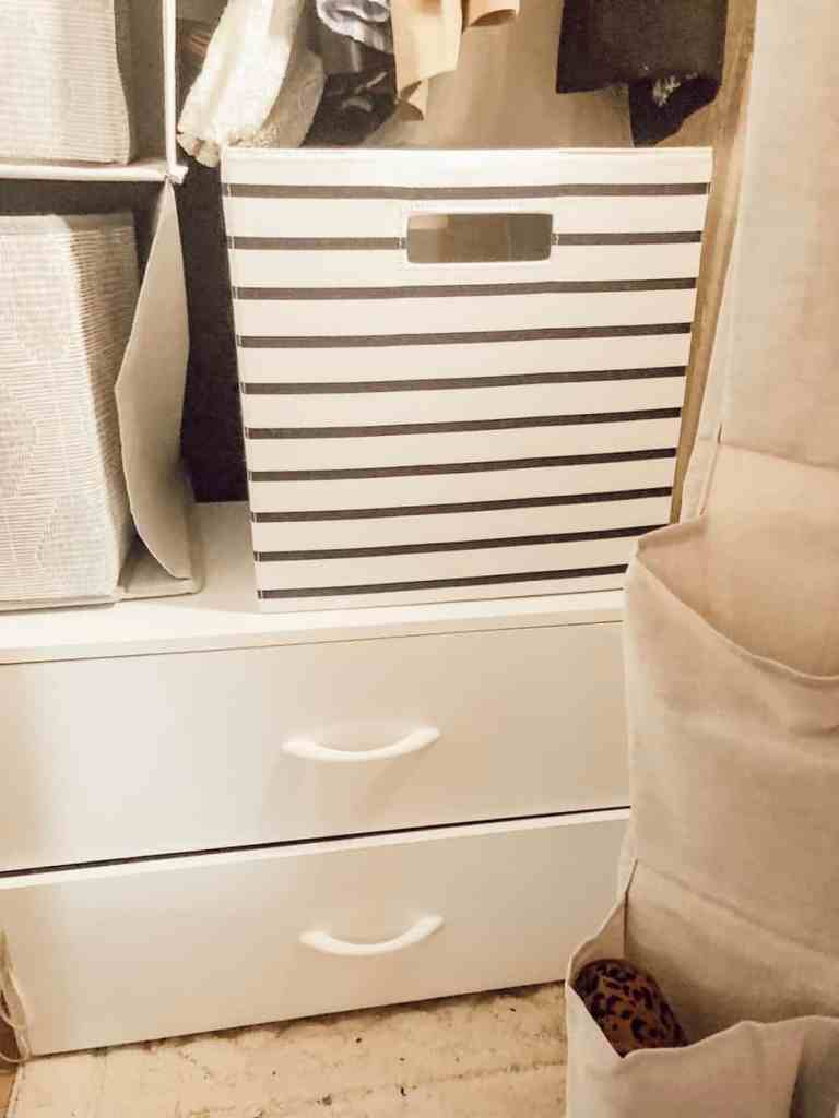 A black and white storage bin on top of the cabinet drawers.