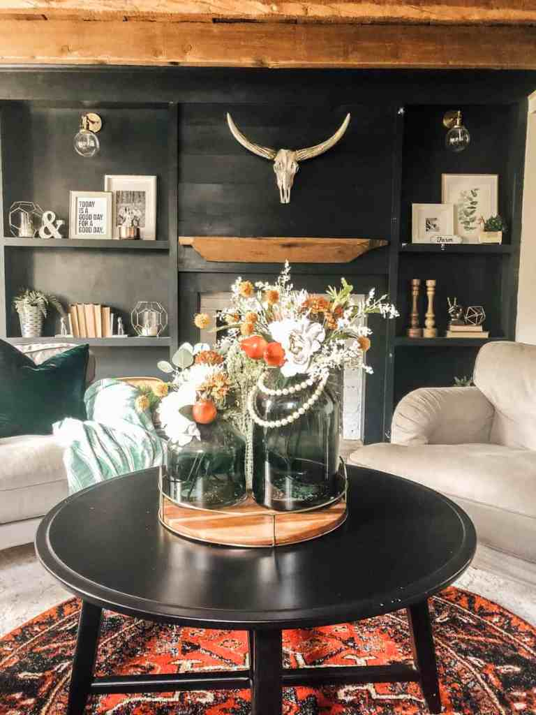 A fall floral arrangement with white, orange flowers on a coffee table in a farmhouse living room.