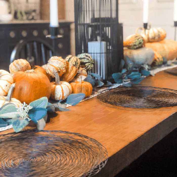 Pumpkins all lined up in the center of a wooden table with a candle in the middle.