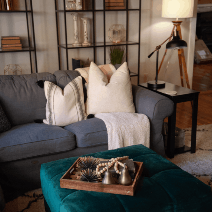 Gray couch with two pillows and a blanket, and on the green ottoman there is a wooden tray with bells and an old book.