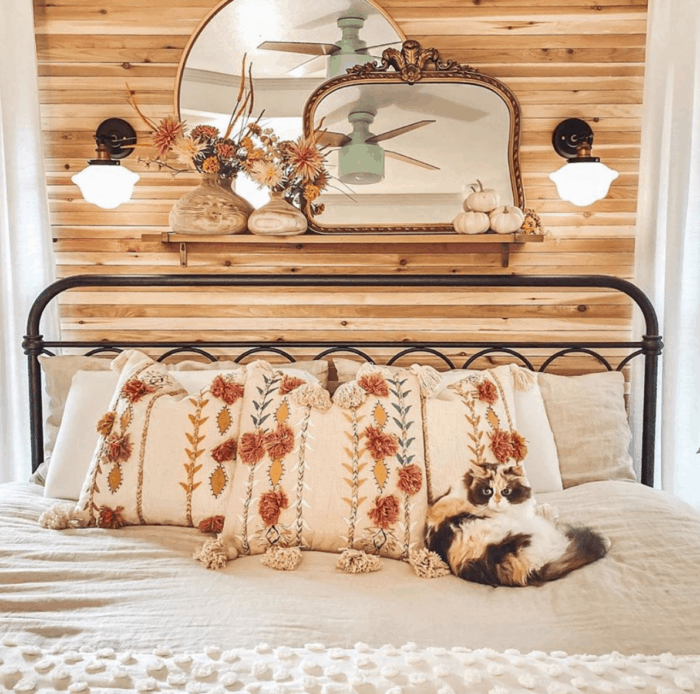 A wrought iron bed with floral pillows and a cat lying on the bed.