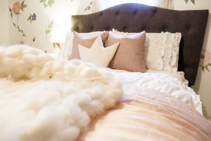 White fluffy blanket on the bed with pillows and floral wallpaper.