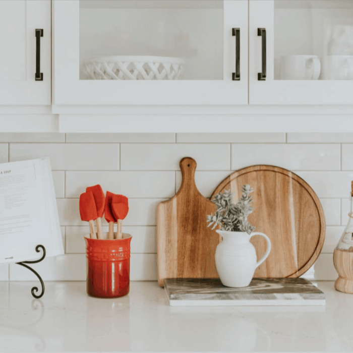 A mostly white kitchen with a red ceramic container with kitchen tools in it, plus a variety of wooden cutting boards and a white pitcher filled with greenery.